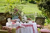 Gedeckter Tisch für den Nachmittagstee im Garten mit Wiesenblumenstrauss und rotweiss gemusterten Stoffen