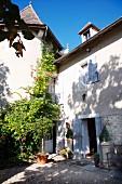 Sonniger Eingangshof eines alten Landhauses mit pastellblauen Fensterläden und blühenden Rankpflanzen an der Fassade