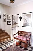 Verzierte, alte Hutschachteln unter traditioneller Holzbank in Eingangsflur mit klassischem schwarzweissem Fliesenmuster