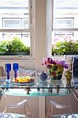 Essplatz mit modernen Designermöbeln aus Stahl, Glas und Plexi vor den alten Schiebefenstern eines englischen Landhauses