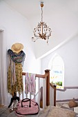 Kleid, Schal und Strohhut an Garderobenständer auf dem oberstem Absatz einer Landhaustreppe; filigraner Kronleuchter mit stilisiertem Blattwerk