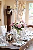 Mit viel Gläsern, silbernen Kerzenleuchtern und zartem Pfingstrosenstrauss festlich gedeckter Tisch in gediegenem Esszimmer