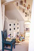 Puppenhaus im englischen Landhausstil, Plüschbären und alter, blauer Kinderstuhl mit Bücherstapel
