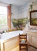 Badezimmerecke im Landhausstil - eingebaute Badewanne am Fenster vor bemalter Wand mit Landschaftsmotiv