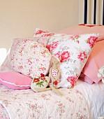 Blumenmuster auf verschieden grossen Kissen auf Bett in ländlichem Stil