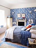 Ländliches Schlafzimmer in Weiss und Blau mit Doppelbett vor Kamin