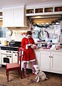 Kind mit Kleid im Nikolausstil und kleiner Hund in ländlicher Küche