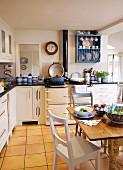 Rustikaler Esstisch mit Gedeck in weisser Landhausküche mit gelblichem Fliesenboden