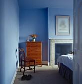 Blau getöntes Schlafzimmer mit Holzkommode neben offenem Kamin