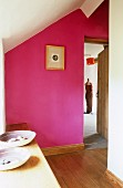 Pinkfarbene Wand in rustikalem Dachgeschoss Flur und Blick durch offene Tür auf Schneiderpuppe