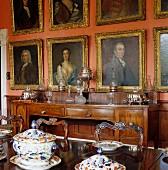 Terrinen und Gedecke auf teilweise sichtbarem Esstisch vor ziegelroter Wand mit Ahnengalerie