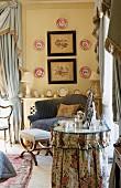 Frisiertisch mit floral gemusterter Husse vor Sessel in Schlafzimmerecke mit gehängten Wandtellern und Bilder mit Blumenmotiven