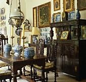 Traditionelles Esszimmer mit dunklen geschnitzten Eichen Stühlen um Tisch mit chinesischen Vasen vor Anrichte mit Aufsatz