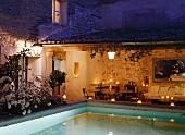 Beleuchteter Pool & überdachte Terrasse eines französischen Landhauses