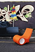 Sofa, parasol and orange lounger in front of house wall painted with graffito