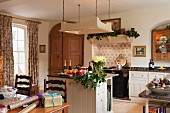 Open-plan, country-house kitchen with free-standing counter below suspended, overhead lighting unit; dining area with wrapped presents in foreground