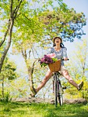 Cheerful woman on bicycle with flowers in basket