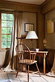 Desk with table lamp in corner of room in Georgian country house with lattice window and floor-length curtains