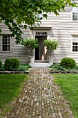 Paved path leading to stylish front door of white-painted, weatherboard country house