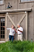 Man and woman talking and gesturing in front of large sliding door in wooden facade in rural surroundings