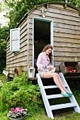 Woman sitting next to box of apples on pale blue ladder leading to nostalgic shepherds' hut amongst greenery