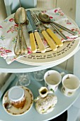 Hellblaues Eckregal mit nostalgischem Besteck und englischem Geschirr im Vintageflair