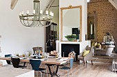 Set dining table and chandelier in modern, loft-style renovated barn with exposed stone wall in background