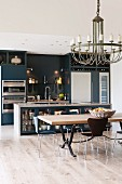 Modern, designer, fitted kitchen with lamps on dark back wall in converted barn with dining table and round chandelier