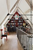 Small library in attic of converted bard with landing balustrade and upholstered wooden chairs