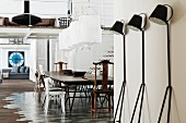 Retro, black metal standard lamps against wall in front of dining area in loft apartment