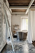 Ladder used as towel rack, vintage bathtub behind curtain in corner of room with whitewashed brick walls and patterned tiled floor