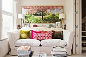 Comfortable sofa with colourful scatter cushions in niche below hand-coloured photograph on wall