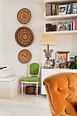 White sideboard decorated with framed photographs and elegant, antique table lamp next to African wall decorations