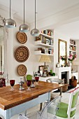 Country-house-style dining table and African wall decorations in open-plan interior