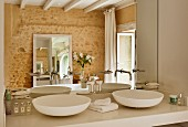 Twin countertop washbasins against mirrored wall in bathroom with stone wall
