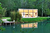 Twilight atmosphere; contemporary studio building beside pond in grounds of historical mill in the Dordogne