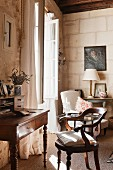 Nostalgic writing area with antique desk and armchair in front of open lattice window in corner