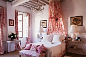 Romantic, shabby-chic bedroom with red and white Toile de jouy fabric curtains, bedroom bench, scatter cushions and canopy