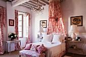 Romantisches Schlafzimmer mit rotweißem Toile-de-Jouy für Vorhänge, Kleiderbank, Kissen und Betthimmel im Shabby-Chic Flair