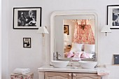 Ensuite bathroom with twin basins on washstand and romantic double bed in country-house style reflected in mirror
