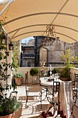 Summery terrace seating area with planters below awning in urban, French courtyard