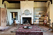 Rustic table with Moroccan tablecloth in spacious, rustic interior with open fireplace in background
