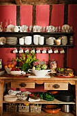 Dishes of vegetables and fruit on wooden dresser below crockery on wall-mounted shelves on red-painted wall