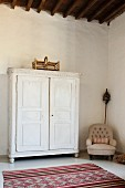 White wooden cupboard in spacious room with high ceiling, armchair and Moroccan rug