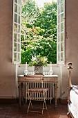 Garden chair and writing desk below open window with view of garden