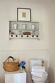 Basket on white, half-height wooden cabinet next to toilet and antique vases on wall-mounted shelves
