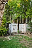 Traditional, rusty metal fence with half-open gate