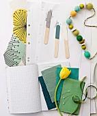 Stoffmuster in grünen Naturfarben, gelbe Tulpe, Holzperlenkette und Holzstäbchen mit Farbproben