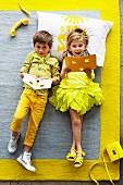 Grey rug with yellow border; little girl and boy wearing shades of yellow lying on rug