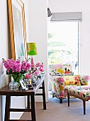 Rustic wall table with vases full of spring flowers; in the background a flower-patterned armchair with an ottoman
